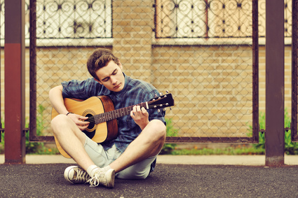 Teenage Boy plays an acoustic guitar