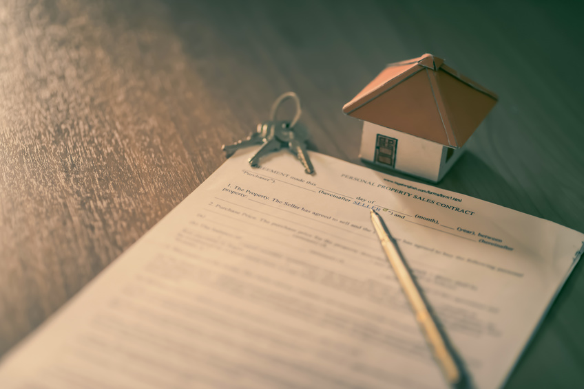 House keys on the rental agreement or the buy home contracts with the real estate property background.